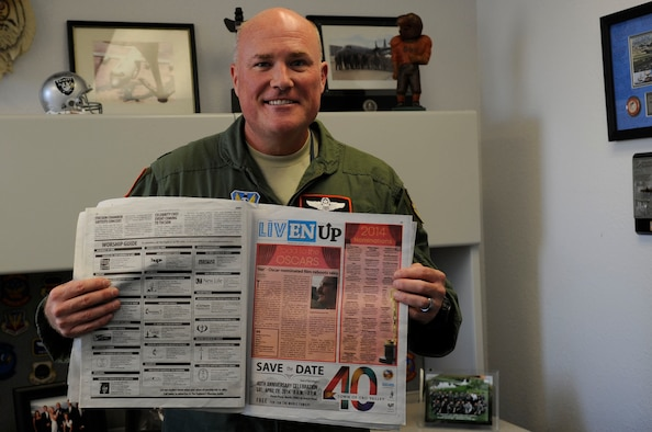 U.S. Air Force Lt. Col. Patrick King, 755th Operations Support Squadron assistant director of operations, holds up a newspaper containing his most recent movie review at Davis-Monthan Air Force Base, Ariz., Jan. 28, 2013. King started writing movie reviews as a hobby on Facebook in 2010 and recently got hired by Explorer Newspaper to write weekly reviews. (U.S. Air Force photo by Airman 1st Class Betty R. Chevalier/released)