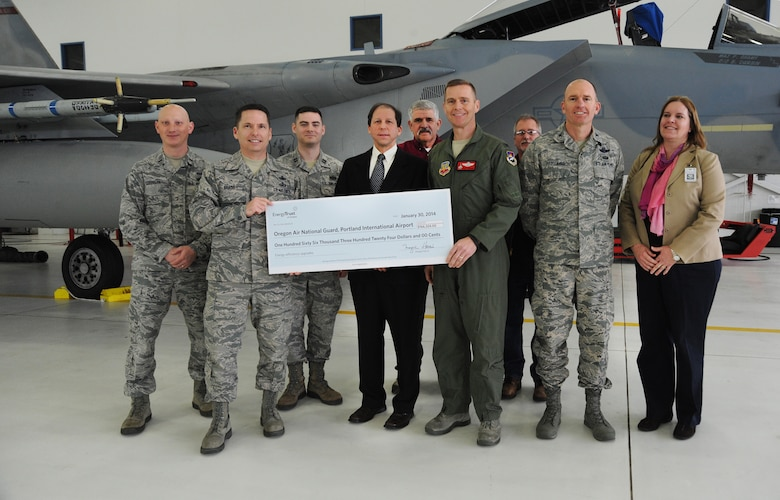 Oregon Air National Guard Chief Master Sgt. Loren Bradd and Col. Rick Wedan, 142nd Fighter Wing Commander, hold a rebate check with Paul West, Director of Energy Programs, and pause for a photograph with other Oregon Air National Guard members, Portland Air National Guard Base staff and other Energy Trust staff during a presentation ceremony held at the Portland Air National Guard Base, Ore., Jan. 30, 2014. (Air National Guard photo by Tech. Sgt. John Hughel, 142nd Fighter Wing Public Affairs/Released)