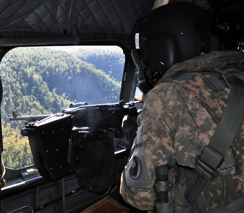 U.S. Army Staff Sgt. Glen Haynie, CH-47 a flight engineer and unit gunnery trainer assigned to Joint Task Force-Bravo's 1-228th Aviation Regiment, fires an M240 machine gun from a CH-47 Chinook helicopter during aerial gunnery training, Jan. 29, 2014.  Members of the 1-228th conduct aerial gunnery training regularly in order to maintain currency and proficiency on the weapon system.  (U.S. Air Force photo by Capt. Zach Anderson)