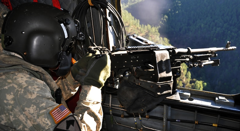 U.S. Army Sgt. Stegan Wood, CH-47 a flight engineer assigned to Joint Task Force-Bravo's 1-228th Aviation Regiment, fires an M240 machine gun from a CH-47 Chinook helicopter during aerial gunnery training, Jan. 29, 2014.  Members of the 1-228th conduct aerial gunnery training regularly in order to maintain currency and proficiency on the weapon system.  (U.S. Air Force photo by Capt. Zach Anderson)