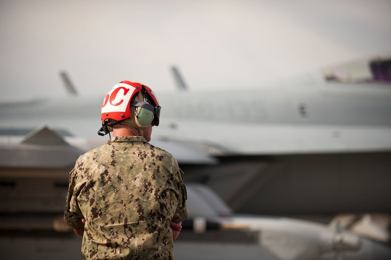 """An aircraft maintainer from the 135th Electronic Attack Squadron, Naval Air Station Whidbey Island, Wash., watches as his assigned aircraft passes by for a training mission after pre-flight checks Jan. 29, 2014, at Nellis Air Force Base, Nev. Joint service aircrews play their part in """"Blue Force"""" operations, supporting the simulated air-war against """"Red Forces"""" organized by the 57th Adversary Tactics Group. (U.S. Air Force photo by Airman 1st Class Joshua Kleinholz)"""