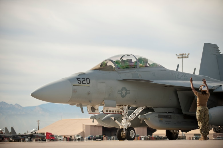 U.S. Navy Petty Officer 3rd Class Micah Smith, 135th Electronic Attack Squadron flight captain, Naval Air Station Whidbey Island, Wash., directs the pilot of an EA-18G Growler out of a parking spot prior to a training mission Jan. 29, 2014, at Nellis Air Force base. Nev. The Boeing EA-18G Growler is an American carrier-based electronic warfare aircraft, a specialized version of the two-seat F/A-18F Super Hornet. Red Flag gives aircrews and air support operations service members from various airframes, military services and allied countries an opportunity to integrate and practice combat operations. (U.S. Air Force photo by Airman 1st Class Joshua Kleinholz)