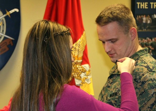 U.S. Marine Corps Sgt. Lance K. Harvey, staff non-commissioned officer in charge of Recruiting Sub-station Frankfort, gets pinned staff sergeant by his wife, Jessica, at the Recruiting Station Louisville headquarters, Jan. 2, 2014. Harvey was meritoriously promoted after winning a Marine Corps Recruiting Command meritorious board against the best recruiters in the command. (Official Marine Corps photo by Sgt. Daniel Angel/Released)