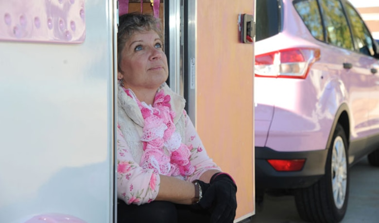 Alison Miller, widow of retired Master Sgt. Chuck Dearing, sits in the doorway of her pink painted teardrop trailer during a travel break Jan. 16, 2014, at the Keesler Air Force Base camp site, Biloxi, Miss. Following Dearing's retirement, the couple sold their home and belongings and traveled the country for four years staying primarily in base lodgings. Prior to the death of her husband, Miller told him that her intent was to continue traveling in a pink painted car so that he could find her while out on the road. (U.S. Air Force photo/Kemberly Groue)