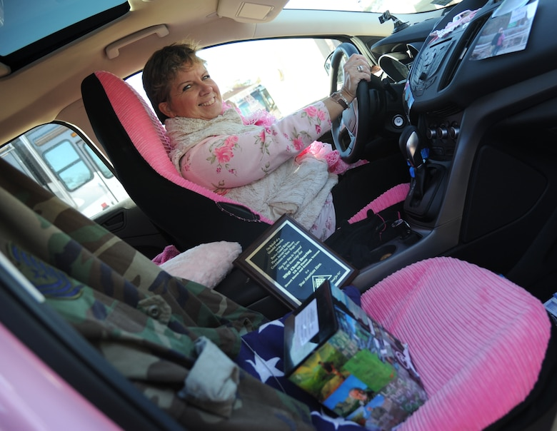 Alison Miller, widow of retired Master Sgt. Chuck Dearing, sits in her pink painted vehicle as military memorabilia is displayed on the passenger seat during a travel break Jan. 16, 2014, at the Keesler Air Force Base camp site, Biloxi, Miss. Prior to the death of her husband, Miller told him that her intent was to continue traveling in a pink painted car so that he could find her while out on the road. (U.S. Air Force photo/Kemberly Groue)