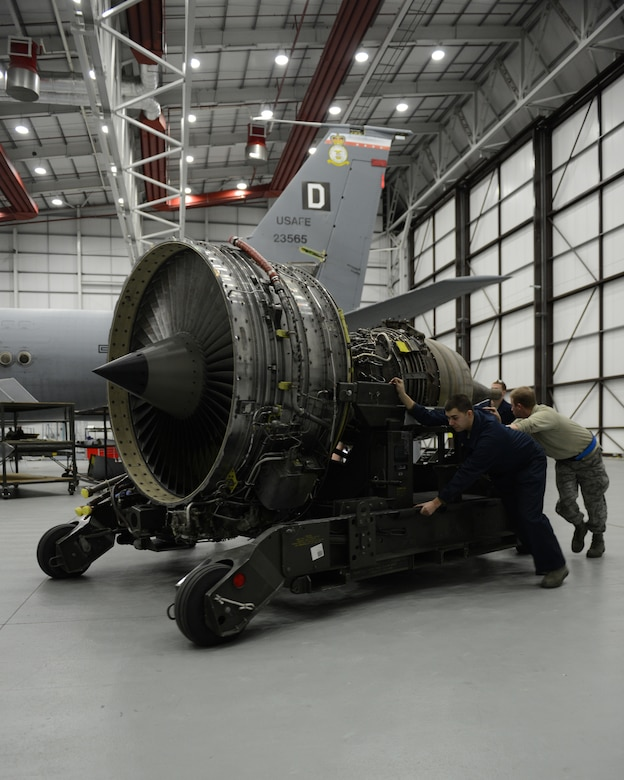 Maintainers push a KC-135 Stratotanker engine into place Jan. 24, 2014, at Royal Air Force Mildenhall, England. Each engine weighs approximately 5,000 pounds and takes several Airmen and an engine trailer to move. Due to their weight, engine trailers and manpower are the easiest method for transporting engines across hangar floors. (U.S. Air Force photo/Airman 1st Class Preston Webb)