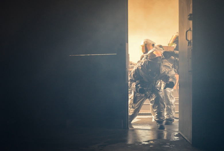 Airman 1st Class Ross Keserich enters a firefighting training scenario Jan. 24, 2014, at Yokota Air Base, Japan. Firefighters practice making low-entrances to ensure they are safe from the heated gases escaping the facility. Keserich is a 374th Civil Engineer Squadron firefighter. (U.S. Air Force photo/Airman 1st Class Meagan Schutter)