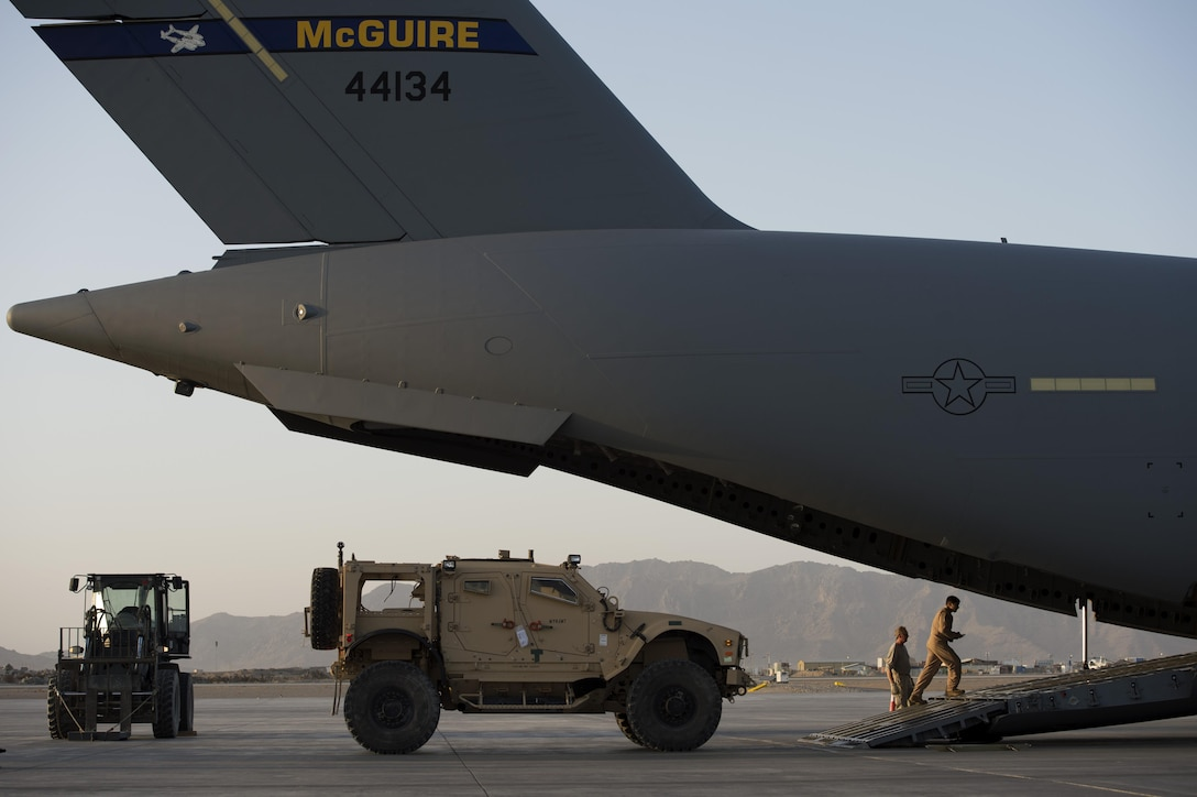 Airmen load a mine-resistant, ambush-protected vehicle on to a C-17 Globemaster III Jan. 25, 2014, at Kandahar Airfield, Afghanistan. Aircrews are working around the clock to support Operation Enduring Freedom retrograde operations, airlifting equipment out of Afghanistan. Equipment is airlifted to regional logistics hubs where it is then sent by sealift to its final location. (U.S. Air Force photo/Tech. Sgt. Jason Robertson)
