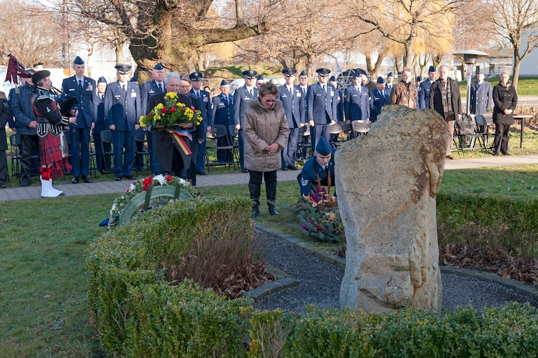 """Else Kriska, a German national bows her head as members place wreaths at the erected memorial for the crew of  a  KC-135 stratotanker crash in Geilenkirchen, Germany, Jan. 10, 2014. Kriska volunteered to take care of the memorial for the crew of """"ESSO 77"""" for the last 15 years."""
