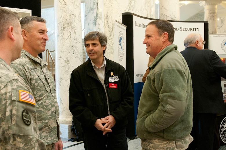 Bill Butticci, a member of the Board of Trustees, talks with Brig. Gen. Richard Turner, right, Assistant Adjutant General, Air, and Col. Michael Garshak, left, Director of Operations from the Idaho Army National Guard, regarding a display about construction for future facilities and the economic impact contributing to the economy during the Military Division Legislative Day held at the State Capitol building in Boise, Idaho Jan. 15. (Air National Guard photo by Master Sgt. Becky Vanshur)