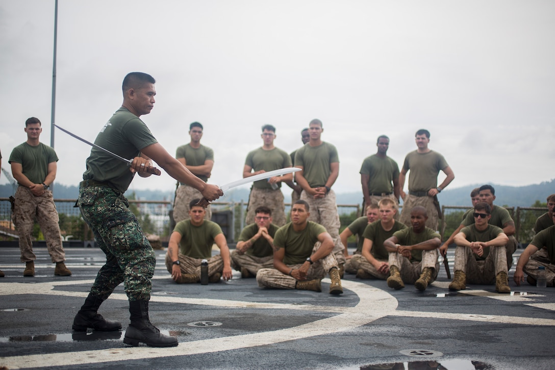 Philippine Marine Master Sgt. Manuel Prado, blademaster assigned to Marine Training Exercise Unit, demonstrates proper blade handling techniques to U.S. Marines assigned to Bravo Company, 1st Battalion, 8th Marine Regiment, during Cooperation Afloat Readiness and Training (CARAT) Philippines 2014.  In its 20th year, CARAT is an annual, bilateral exercise series with the U.S. Navy, U.S. Marine Corps and the armed forces of nine partner nations including Bangladesh, Brunei, Cambodia, Indonesia, Malaysia, the Philippines, Singapore, Thailand and Timor-Leste.