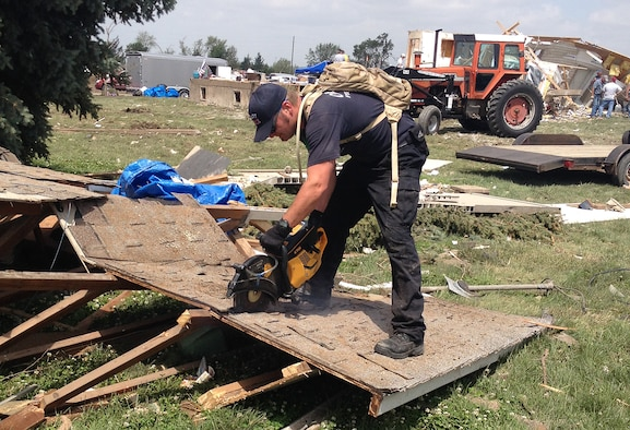 Ron Dawson, cuts debris with a K-12 saw June 18, 2014, in Pilger, Nebraska. Dawson was part of a group of volunteers from Offutt who helped with the cleanup efforts in Pilger following a tornado that destroyed approximately 75 percent of the town, June 16, 2014. Dawson is a firefighter from the 55th Civil Engineering Squadron. (Courtesy photo)