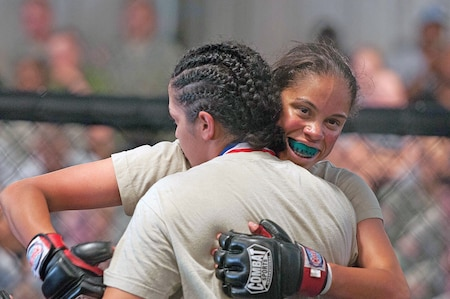 Natasha Ramos, STB, 1st ABCT, 1st Inf. Div., hugs her opponent, Jenny Balluo, 193rd BSB, 4th MEB, after their battle in the cage June 12 at Fort Riley as part of the Victory Week Combatives Tournament. Ramos defeated Ballou and was crowned the 110-pound weight class champion.