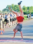 Capt. Mark Vidotto crosses the finish line of the Victory Week 10-Miler June 11 at Custer Hill. Vidotto celebrated his run with a handstand at the finish line.