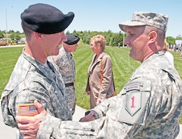 Col. Mike Morgan, 1st Inf. Div. chief of staff, and Brig. Gen. Sean P. Swindell, 1st Inf. Div. deputy command general for maneuver, embrace each other after the Victory Retreat Ceremony June 13 at Fort Riley. During the ceremony, the division bid farewell to Morgan and Brig. Gen. Frank Muth, 1st Inf. Div. deputy commanding general for support.