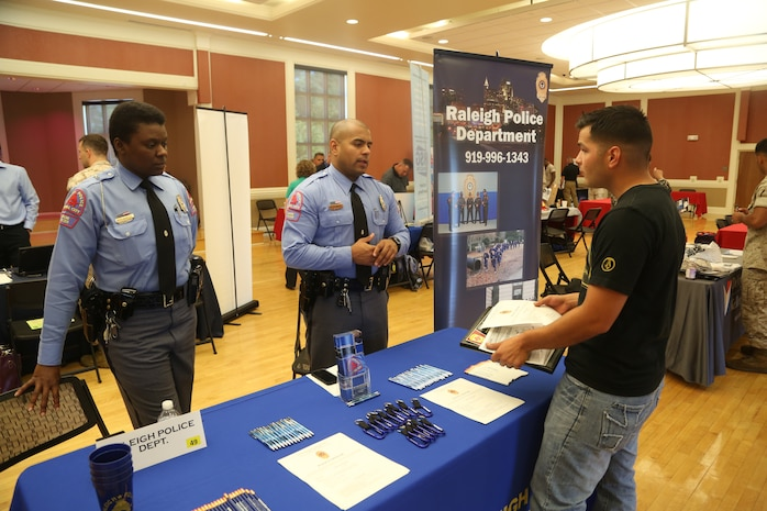 Representatives from the Raleigh Police Department provide an attendee with future job opportunities at the National Vocational and Technical Career Hiring Expo at Marston Pavilion aboard Marine Corps Base Camp Lejeune, June 19. Approximately 60 companies and 500 job seekers attended the expo for education information and job openings.