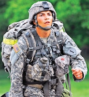 Spc. Luis Perez, a medic with HHT, 5th Sqdn., 4th Cav. Regt., 2nd ABCT, 1st Inf. Div., marches toward the finish line of the 12-mile ruck march event of the EFMB testing June 9 at Fort Riley. Perez was one of only 14 of 139 Soldiers who earned their EFMB after a weeklong set of physical and mental tests.