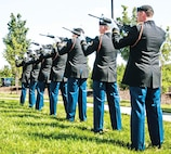 A seven-man firing party conducts a rifle volley during a June 12 ceremony at Victory Park.