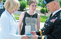 "Maj. Gen. Paul E. Funk II, commanding general, 1st Inf. Div. and Fort Riley, right, is handed a Congressional Medal of Honor from Cathy Ehlers Metcalf, left, and Katherine Metcalf, center, after a June 12 ceremony at Victory Park. The event honored the division's recent Medal of Honor recipients and Gold Star families by unveiling their memorial stones within the park. Metcalf is the granddaughter of Staff Sgt. Walter D. Ehlers, who received the nation's highest award for valor in 1944 for his actions in Goville, France, died Feb. 20. He was the remaining Medal of Honor recipient of the ""Big Red One."""