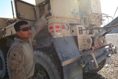 Corporal Anthony Casares, a wrecker operator with Marine Wing Support Squadron 274, operates a Logistics Vehicle System Replacement MKR15 wrecker while removing an empty 210,000-gallon bulk fuel bladder aboard Camp Bastion, Afghanistan, June 28, 2014. In three hours' time, more than 15 Marines with MWSS-274 and 15 contractors removed the last one of eight non-Marine Corps owned bulk fuel bladders at the bulk fuel site. (U.S. Marine Corps photo by Cpl. Cody Haas/ Released)