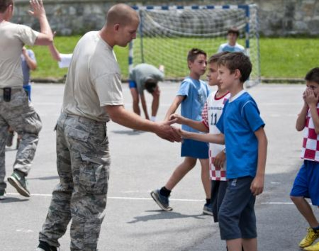 Staff Sgt. Jake Pudlick slaps hands with kids after a brief soccer game outside an elementary school in Ogulin, Croatia, June 18, 2014. The school bathrooms are being renovated by Airmen from the 133rd Civil Engineering Squadron, 148th Civil Engineering Squadron, and 219th Red Horse Squadron in partnership with the Croatian Army. (U.S. Air National Guard photo by Staff Sgt. Austen Adriaens)