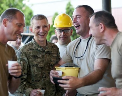 Senior Master Sgt. Kurt Huver, 133rd Civil Engineering Squadron, shares videos on his cellphone with members of the Croatian Army outside an elementary school in Ogulin, Croatia, June 18, 2014. The school bathrooms are being renovated by Airmen from the 133rd Civil Engineering Squadron, 148th Civil Engineering Squadron, and 219th Red Horse Squadron in partnership with the Croatian Army. (U.S. Air National Guard photo by Staff Sgt. Austen Adriaens)