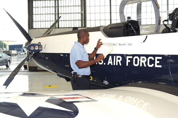 Mr. Louis Marcy, a member of the 12th Flying Training Wing Maintenance Directorate, unveils Col. Matthew C. Isler's name on a T-6 aircraft during the change of command ceremony here June 25. As part of an Air Force tradition, one of the aircraft is painted with the new commander's name.  (U.S. Air Force photo by Melissa Peterson)