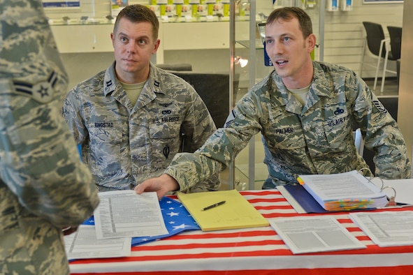 U.S. Air Force Capt. Erik Ringstad, 52nd Component Maintenance Squadron commander and Niceville, Fla., native, seated left, and U.S. Air Force Master Sgt. Timothy Palmer, 52nd CMS assistant accessory flight chief and Hobart, Ind., native, seated right, provide voter registration materials to U.S. Air Force Airman 1st Class Tyler Neff, a 52nd Security Forces Squadron patrolman and Bryson, Texas, native, at an information booth at the base exchange at Spangdahlem Air Base, Germany, June 30, 2014. The Federal Voting Assistance Program helps service members and their families with registration and voting guidelines across the United States.  (U.S. Air Force photo by Staff Sgt. Joe W. McFadden/Released)