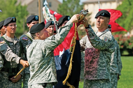 """Col. John W. Reynolds III and Command Sgt. Maj. Michael F. Evans, 1st ABCT, command team, case the """"Devil"""" brigade's colors June 18 during a ceremony at Cavalry Parade Field. The brigade's Soldiers are set to serve a nine-month deployment to Kuwait in support of Operation Spartan Shield."""