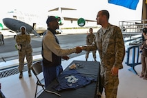Phil Bates, left, Seattle Seahawks wide receiver, thanks Staff Sgt. Ramsey Tesch  for his military service July 1, 2014, after signing a shirt for his Airman leadership school during the 2014 Seattle Seahawks 12 Tour at Joint Base Lewis-McChord, Wash. Bates is part of the 12 Tour traveling through the Pacific Northwest thanking fans for their support during the championship season. Tesch is a 62nd Aerial Port Squadron information controller. (U.S. Air Force photo/Staff Sgt. Russ Jackson)