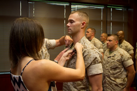 Kerry Johnsen pins the rank of Staff Sergeant on her husband, Staff Sgt. Nicholas C. Johnsen, during a meritorious promotion ceremony at the Military Entrance Processing Station in Milwaukee, Wis., July 2, 2014.  Staff Sgt. Johnsen was the 9th Marine Corps District's Officer Selection Assistant of the year for fiscal year 2013.