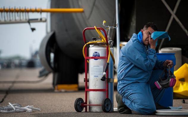 An Airman from the 910th Airlift Wing, Youngstown Air Reserve Station, Ohio, wipes his face after removing his respiratory protection mask June 25, 2014, on Joint Base Charleston, S.C. The C-130 Hercules crew sprayed for mosquitos at the base and maintains the Defense Department's only large-area, fixed-wing aerial spray capability to control disease-carrying and pest insects. (U.S. Air Force photo/Airman 1st Class Clayton Cupit)