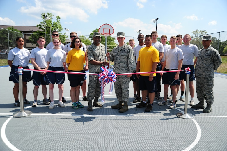 Col. Bill Knight, 11th Wing/Joint Base Andrews commander, and Chief Master Sgt. William Sanders, 11th WG/JBA command chief, pose for a ribbon cutting with dorm residents for official opening of the new volleyball and basketball court at Joint Base Andrews, Md., June 26, 2014. (U.S. Air Force photo/Airman 1st Class Joshua R. M. Dewberry)