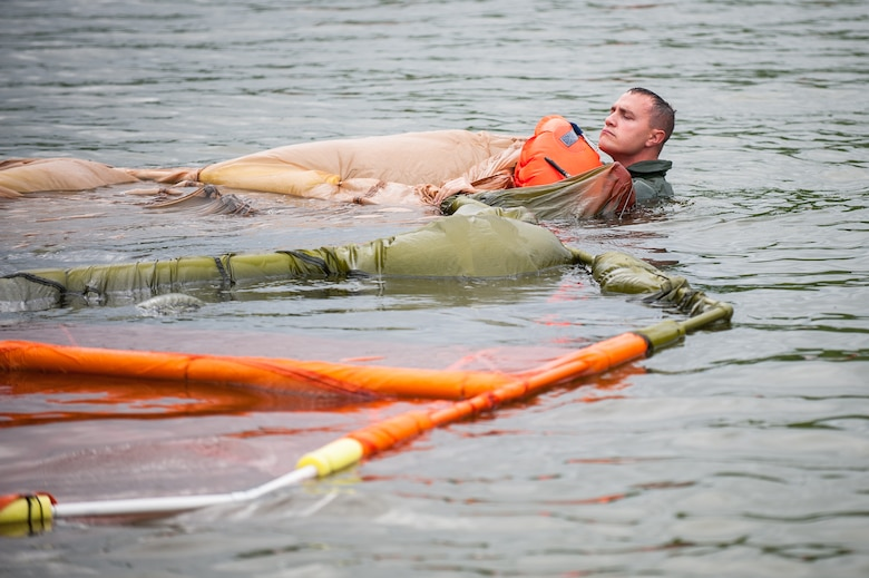 Tech. Sgt. Jerry Passafiume, a loadmaster in the Kentucky Air National Guard's 165th Airlift Squadron, extricates himself from underneath a floating parachute during water survival training at Taylorsville Lake in Taylorsville, Ky., on June 5, 2014. The training also covered land survival techniques and orienteering. (U.S. Air National Guard photo by Maj. Dale Greer)