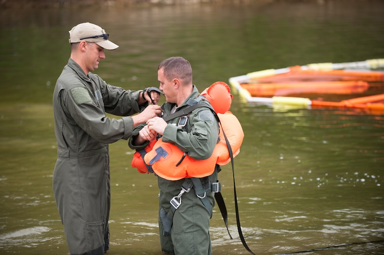 Master Sgt. Brad Simms (left), a loadmaster in the Kentucky Air National Guard's 165th Airlift Squadron, helps fellow loadmaster Tech. Sgt. Jerry Passafiume strap on a parachute harness prior to water survival training at Taylorsville Lake in Taylorsville, Ky., on June 5, 2014. The training also covered land survival techniques and orienteering. (U.S. Air National Guard photo by Maj. Dale Greer)