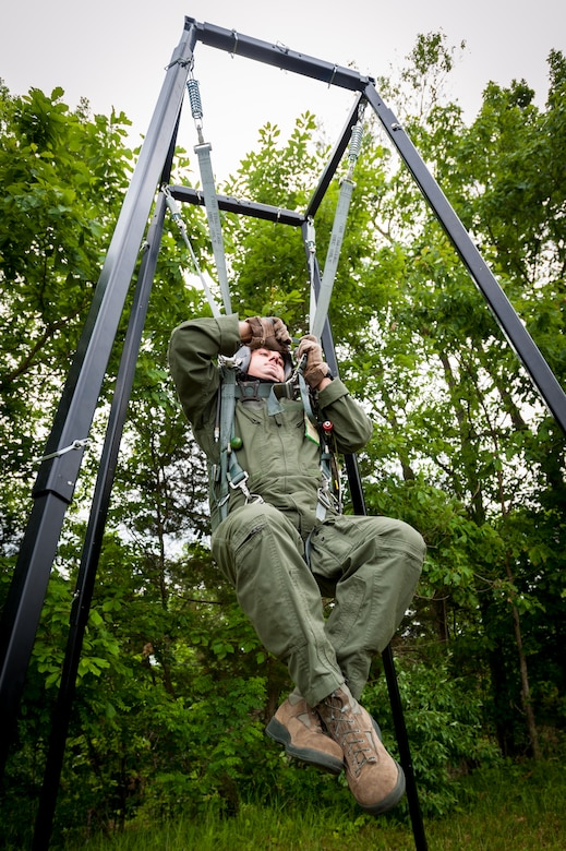 Master Sgt. Brad Simms, a loadmaster in the Kentucky Air National Guard's 165th Airlift Squadron, works to lower himself from a training apparatus during survival training at Taylorsville Lake in Taylorsville, Ky., on June 5, 2014. The exercise is designed to train pilots on proper procedures should they become caught in a tree while parachuting to the ground. (U.S. Air National Guard photo by Maj. Dale Greer)