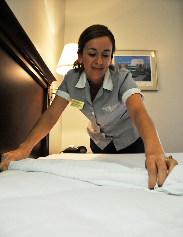 Carolina McGarrigle, 509th Force Support Squadron housekeeper, makes a bed at Whiteman Air Force Base, Mo., June 25, 2014. Preparing rooms are essential to providing presentable living areas for guests. (U.S. Air Force photo by Airman 1st Class Keenan Berry/Released)