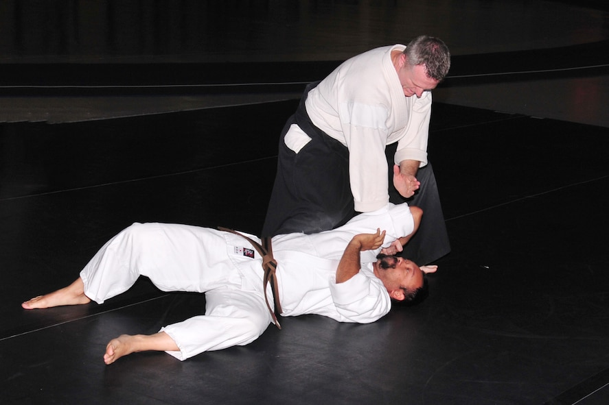 U.S. Navy Reserve Lt. Cmdr. Lloyd McWhirt demonstrates an Akido throwing technique on his assistant, Brad Clear, May 22 at the field house on Offutt Air Force Base, Nebraska. McWhirt runs his own Dojo in downtown Omaha and gives free Aikido lessons to the Offutt community at the Offutt Field House. (U.S. Air Force photo by D.P. Heard/Released)