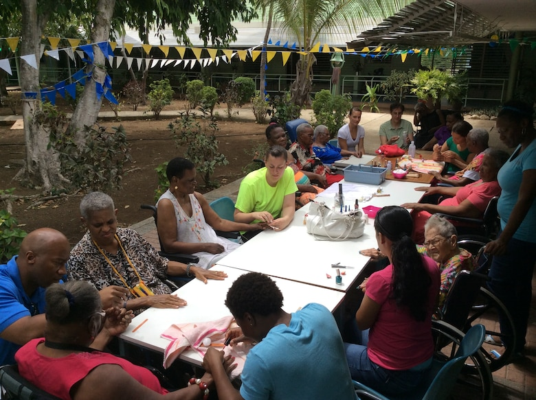 Six female volunteers from the U.S. Forward Operating Location spent several hours at Betesda Nursing Home in Betesda, Curacao, July 1, 2014. The volunteers offered the female residents a relaxing morning of manicures and spoke to the residents about life, family and culture, bringing the warmth of friendship directly to elders with one-on-one interaction. This informal volunteer partnership with Betesda helps emphasize a continuum of care for the Curacao senior community. Volunteers from the US FOL often donate time and resources to various areas and programs on the island, in order to express appreciation for the wonderful hospitality received from the citizens of Curacao. (Courtesy Photo)