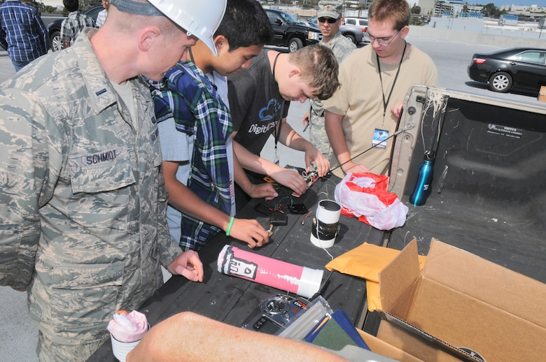 "Students from five local area high schools teamed up with Space and Missile Systems Center mentors atop of the Los Angeles AFB, 7th floor parking lot, where they launched payloads and recorded flight data and or went back to the drawing board to make improvements, Jun 16, 2014. The STEM event is part of the SMC 60th Anniversary as the six teams were responsible for ""fundamental design practices to... develop imaging and data acquisition payloads to be launched from the roof of the parking garage. Students were responsible for designing, building, integrating and testing electronics packages into a bus structure capable of surviving launch, flight and recovery. A small parachute will be deployed from each payload to increase time aloft to gather data. Data and imagery will be acquired and judges will evaluate the payloads on functionality, structural integrity and aesthetics"". (Photo by Joe Juarez)"