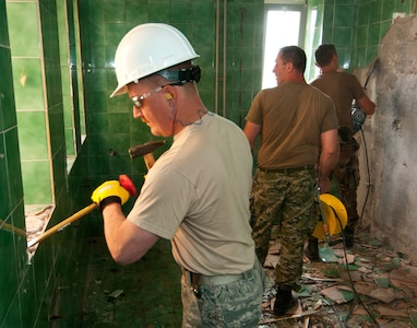 U.S. Air Force Master Sgt. Steven Virnig, 133rd Civil Engineering Squadron, removes tile from an elementary school bathroom in Ogulin, Croatia, June 17, 2014. The school bathrooms are being renovated by Airmen from the 133rd and 148th Civil Engineering Squadron, and 219th Red Horse Squadron in partnership with the Croatian Army. Croatia is a Minnesota State Partner under the National Guard State Partnership Program.