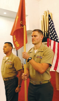 Capt. Thomas F. Cutsinger (right), accepts the guidon from Maj. Alexander J. Vanston at the Headquarters Company East's change of command ceremony held at the Marine Corps Logistics Base Albany's Base Chapel Annex, Friday. Vanston will take over as Marine Corps Logistics Command's staff secretary.