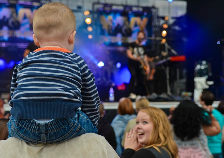A child watches as David Cook, American Idol-winning musician, performs on the stage during the Belgian-American Friendship Day at Kleine Brogel Air Base, Belgium, June 27, 2014. Cook performed the free concert as part of his worldwide tour sponsored by Navy Entertainment and Armed Forces Entertainment. (U.S. Air Force photo by Staff Sgt. Joe W. McFadden/Released)