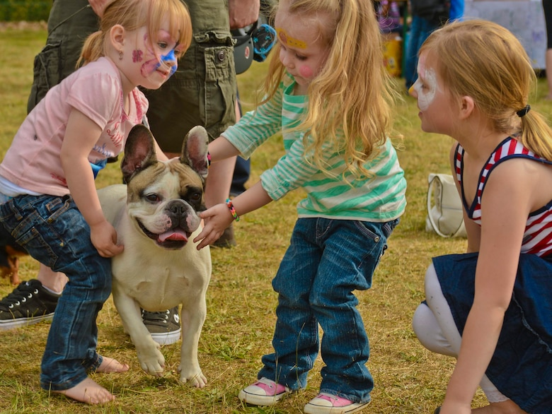Children pet Roskoe, a French Bulldog, during the Belgian-American Friendship Day at Kleine Brogel Air Base, Belgium, June 27, 2014. Belgian and American children had opportunities to get their faces painted, play in a bouncy castle and play with Frisbees during the complementary event. (U.S. Air Force photo by Staff Sgt. Joe W. McFadden/Released)