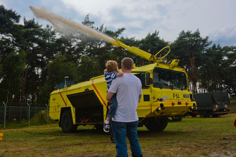 U.S. Air Force Staff Sgt. Evan McLelland, a 701st Munitions Support Squadron NCO and Boynton Beach, Fla., native, holds his son, Aiden, 5, as they watch a Belgian Air Component fire truck shoot its water cannon during the Belgian-American Friendship Day at Kleine Brogel Air Base, Belgium, June 27, 2014.  The Belgian Armed Forces maintain the installation which houses the Airmen of the 701st MUNSS. (U.S. Air Force photo by Staff Sgt. Joe W. McFadden/Released)