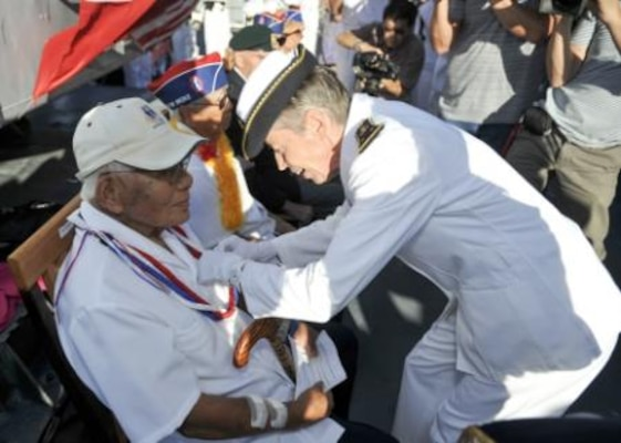 Aboard the French Floréal-class frigate FS Prairial berthed in Pearl Harbor, Hawaii, Rear Adm. Anne Cullere, commander in chief of French forces in the Pacific, presents U.S. World War II veteran Shuji Akiyama, who'd fought with the 100th Battalion, the French Nation Order of the Legion of Honor during a July 2, 2014, ceremony in which six other veterans also received the honor. For more than a decade the government of France has presented the Legion of Honor to U.S. veterans who participated in the liberation of France during World War II. The ceremony took place during Rim of the Pacific, the world's largest international maritime exercise. U.S. Navy photo by Petty Officer 1st Class David Kolmel