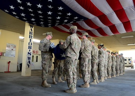 """U.S. Air Force Airmen fold an American flag during a folding ceremony at Craig Joint Theater Hospital in Bagram Airfield, Afghanistan July 4, 2014. A newly dedicated American flag replaced the hospital's retired flag which was first raised on July 4, 2011. The new flag hangs on the ceiling of the hospital's main patient entry also known as """"Warrior's Way."""" (U.S. Air Force photo by Staff Sgt. Evelyn Chavez/Released)"""