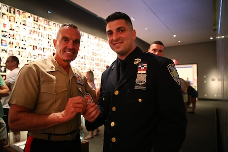 Brigadier Gen. Vincent Coglianese, 1st Marine Logistics Group Commanding General, gives Officer Joseph Maarleveld, of the New York Port Authority Police , his coin during a tour of the 9/11 Museum in New York, June 25, 2014. Brigadier Gen. Coglianese traveled to New York City to officiate Col. James Maxwell's retirement ceremony. Maxwell, a New York State trooper and Marine, served 32 in the Marine Corps. During his career he served in Operation Desert Shield, Operation Desert Storm and Operation Enduring Freedom.