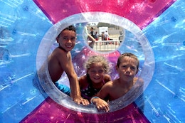 Seven-year-olds Luis, Jayden and Jaylxon spin inside a floating intertude at the Beach Bash at Del Mar Beach here July 4.   
