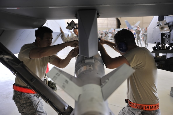 Staff Sgt. Trung Dinh, left, and Senior Airman Devin Milburn attach a GBU-12 Paveway laser guided bomb onto an MQ-9 Reaper during a load crew competition June 30, 2014, at Creech Air Force Base, Nev. The competition consists of two three-man teams from different aircraft maintenance units competing against each other in order to build skills and promote camaraderie. Dinh is a 432nd Aircraft Maintenance Squadron weapons load crew chief and Milburn is a 432nd Aircraft Maintenance Squadron support technician.  (U.S. Air Force photo/Airman 1st Class Christian Clausen)